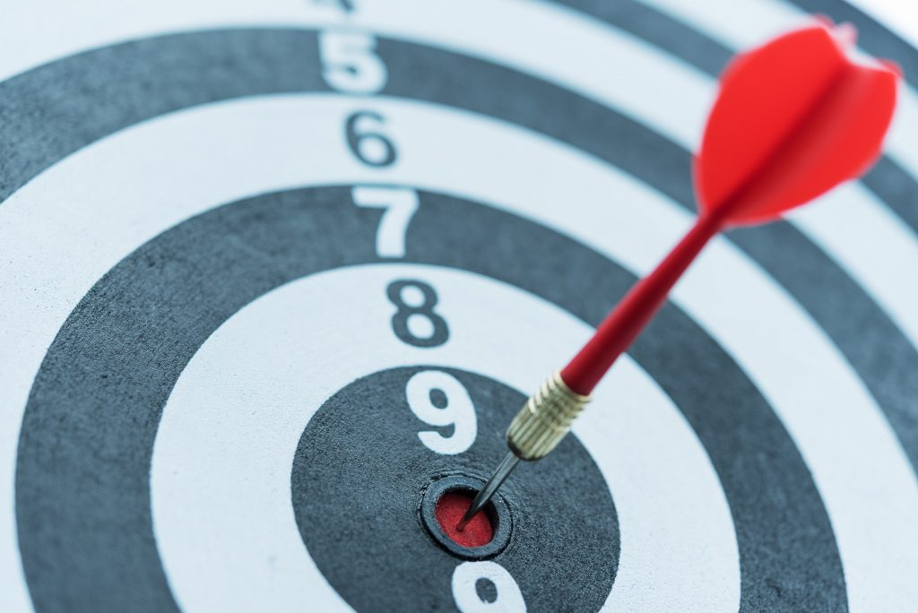 Dart target arrow hitting on bullseye with sun light